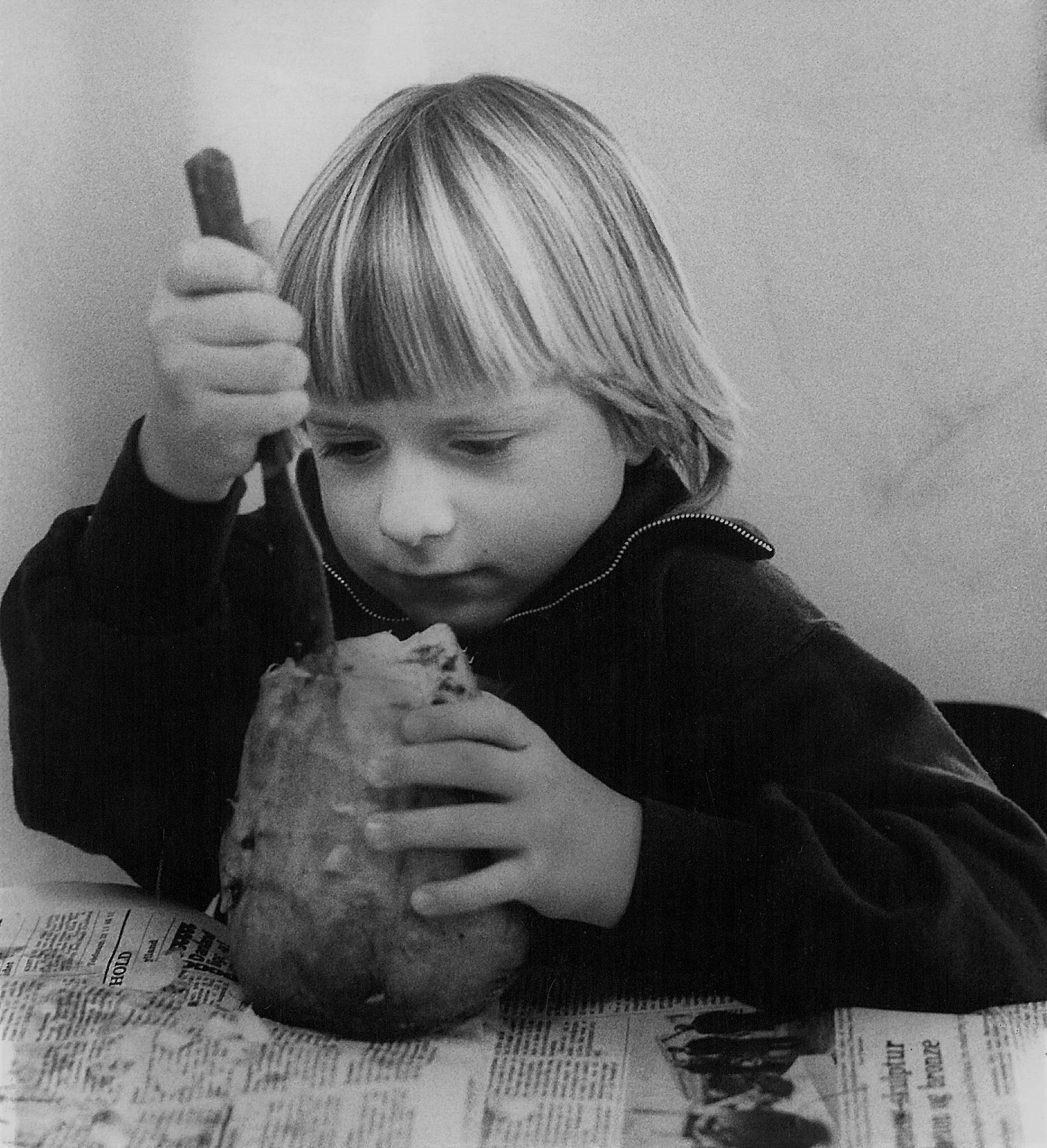 Et barn skærer en roelygte