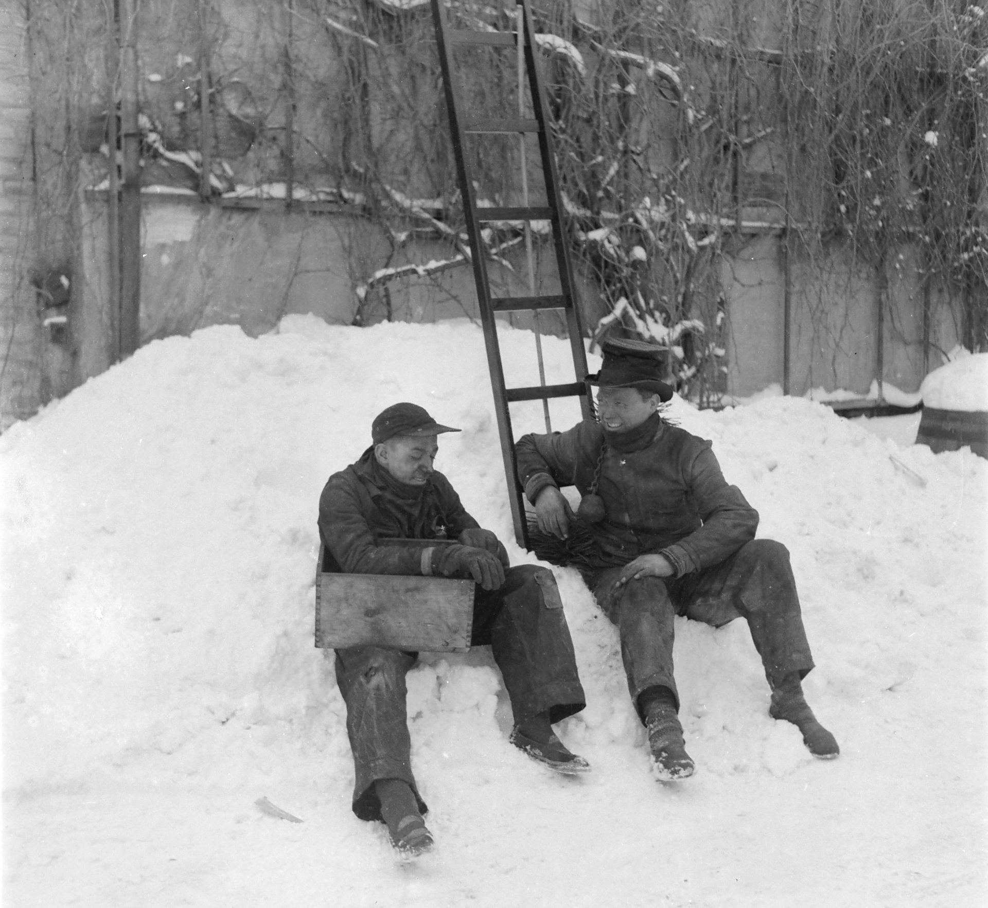 Skorstensfejer sidder i en bunke sne