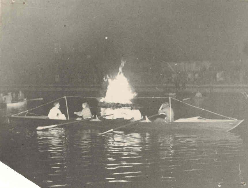 Et bål på vandet med robåde omkring