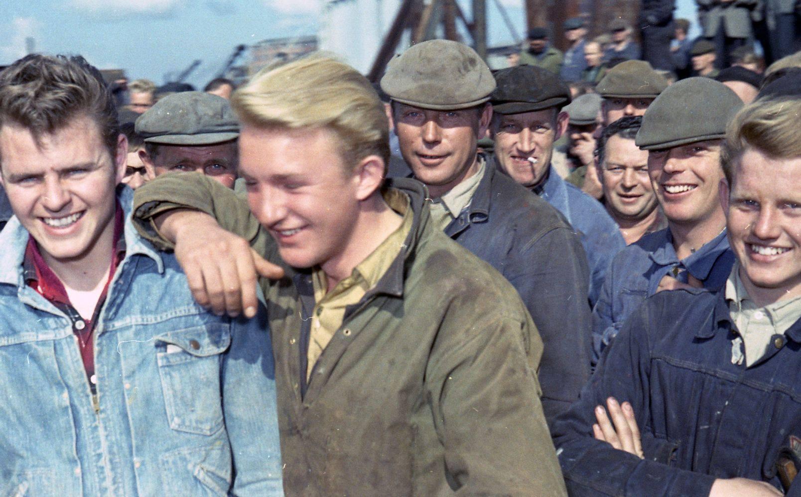 Unge værftsarbejdere smiler til fotografen